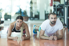 Gym man and woman push-up strength pushup with dumbbell in a fitness workout Royalty Free Stock Image