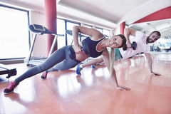 Gym man and woman push-up strength pushup with dumbbell in a wor Royalty Free Stock Image