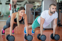 Gym man and woman push-up strength pushup with dumbbell in a workout Stock Photo