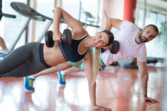 Gym man and woman push-up strength pushup with dumbbell in a workout Stock Photos