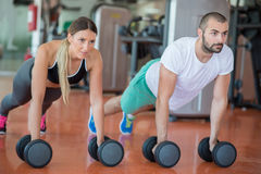 Gym man and woman push-up strength pushup with dumbbell in a workout Royalty Free Stock Image