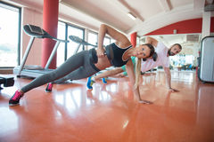 Gym man and woman push-up strength pushup with dumbbell in a workout Stock Image