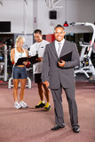 Gym manager and trainers. Happy gym manager and trainers inside gym Stock Photography