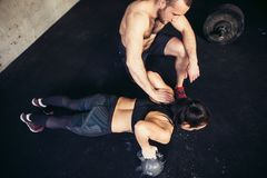 Trainer man and woman push-up strength pushup in a fitness workout. Gym men and women push-up strength pushup in a fitness workout royalty free stock photography