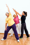 Gym monitor helping senior ladies with exercise. Stock Images