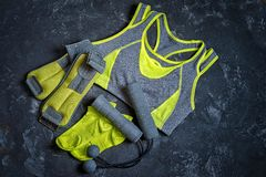 Gym outfit. Workout clothing in gray and yellow colors on a dark background with copy space. Sport accessories and fashion, Healthy lifestyle Stock Photos