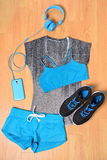 Gym outfit - workout clothing and smartphone. Gym outfit - workout clothing, running shoes, headphones and smartphone to listen to music while working out at the Stock Photography