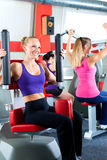 Gym people doing strength or fitness training. Three young women doing strength or sports training in gym for a better fitness Stock Photo