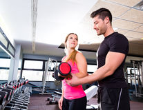 Gym personal trainer man with dumbbell woman Royalty Free Stock Images