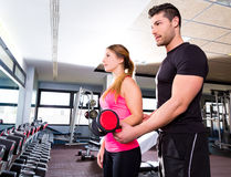 Gym personal trainer man with dumbbell woman Stock Photo