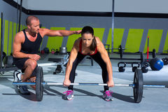 Gym personal trainer man with weight lifting bar woman. Workout in crossfit exercise Royalty Free Stock Image