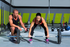 Gym personal trainer man with weight lifting bar woman. Workout in crossfit exercise Stock Photo