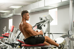 At gym. Photo of sexy guy trains on simulator Royalty Free Stock Photo