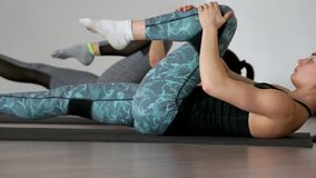 In the gym during the pilates exercise lying on the gym mats two girls lying on their back alternately pull their knees. To the chest stretching the muscles of stock video footage