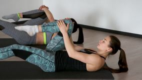 In the gym during the pilates exercise lying on the gym mats two girls lying on their back pulling their knees to the. Chest stretching the muscles stock video
