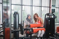 Gym sadzający noga kędzioru maszynowego ćwiczenia kobiet muzułmański hijab Zdjęcie Stock