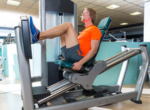 Gym seated leg press machine blond man workout Royalty Free Stock Image