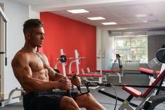 At gym. Sexy shirtless guy exercising on simulator Stock Photo