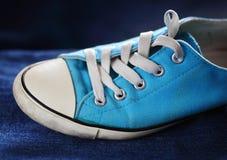 Gym shoe. Blue gym shoe on jeans stock photo