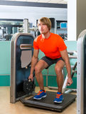 Gym squat machine exercise workout blond man Stock Photos