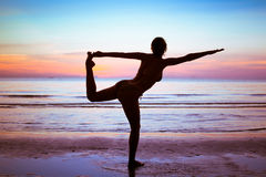 Gym and stretch. Silhouette of young woman doing gym and stretch exercises on the beach Stock Images