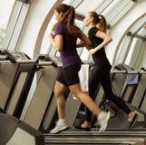 Gym strzelał - młode kobiety biega na maszynach, karuzela Zdjęcie Royalty Free