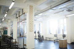 Gym in Sunlight. Background image of various equipment in gym: exercise stands with climbing rope and barbell benches in empty sunlit hall Royalty Free Stock Photos