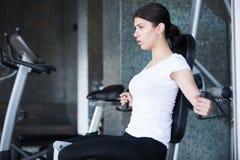 gym szkolenia ciężaru kobieta Ćwiczyć dalej ciągnie puszka ciężaru maszynę Kobieta robi Ups ćwiczy podnośnych dumbbells zdjęcie stock