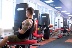 At gym. Tattooed bodybuilder trains on simulator Royalty Free Stock Photography
