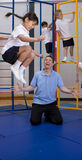 Gym teacher watching school girl jumping off climbing equipment Royalty Free Stock Photos