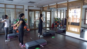 In the gym three women doing workout in front of step aerobics. stock video footage