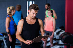 Gym trainer with clipboard. While people standing in background Royalty Free Stock Image