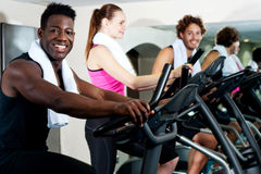 Gym trainer exercising along with his trainees Stock Image