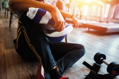 The gym trainer sitting on the ground and hold Small towel. A dumbbell near the gym trainer. stock photography