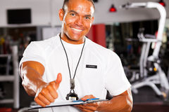 Gym trainer thumb up. Happy male gym trainer giving thumb up Royalty Free Stock Image