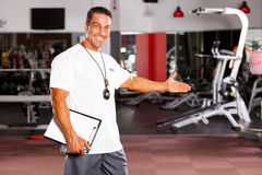 Gym trainer welcome customer. Happy male gym trainer welcome customer Royalty Free Stock Images