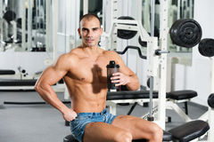 Gym training. Young caucasian bodybuilder in the gym, holding a protein shake Royalty Free Stock Images