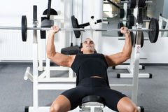 Gym training. Young bodybuilder training in the gym: chest - barbell incline bench press - wide grip Stock Photography