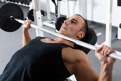 Gym training. Young bodybuilder training in the gym: chest - barbell incline bench press - wide grip Stock Image