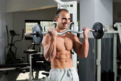 Gym training. Young bodybuilder training in the gym - e-z bar biceps curl Royalty Free Stock Photos