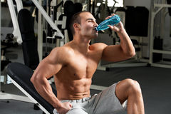 Gym training. Young caucasian bodybuilder in the gym, drinking a bottle water Royalty Free Stock Photos