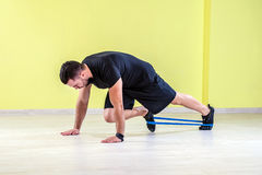 Gym training. Guy working out with rubber band in studio gym Stock Photos