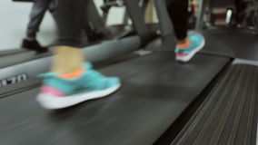 Gym, training on a treadmill, a girl in her. Moving forward on a treadmill at the gym. the athlete moves rapidly and vigorously, favorite shoes, in any gym, that stock footage