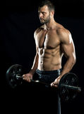 Gym training workout. Man doing weight lifting in gym on black background Royalty Free Stock Photos