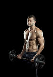 Gym training workout. Man doing weight lifting in gym on black background Stock Photo