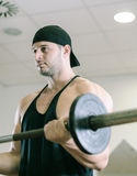 Gym training workout. Young adult man is working out in gym Royalty Free Stock Images