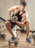 Gym training workout. Young adult man is working out in gym Royalty Free Stock Photography