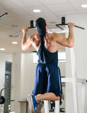 Gym training workout. Young adult man is working out in gym Stock Photos