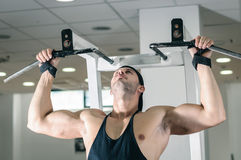Gym training workout. Young adult man is working out in gym Royalty Free Stock Image