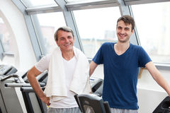 Gym training, young man and his father Stock Photos